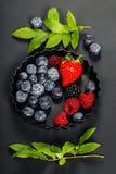 在黑暗的背景的新鲜的莓果 免版税图库摄影