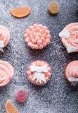 在黑暗的背景的桃红色杯形蛋糕用面粉 免版税库存图片