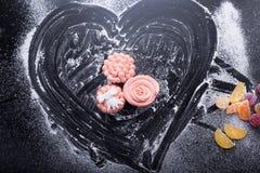 在黑暗的背景的桃红色杯形蛋糕用面粉 图库摄影