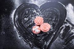 在黑暗的背景的桃红色杯形蛋糕用面粉 库存图片