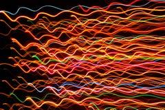 在黑暗的背景的波浪多彩多姿的发光的线 库存图片