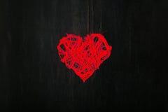 在黑暗的背景的爱华伦泰红色心形的花圈 库存图片