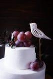 在黑暗的背景的白色两层蛋糕 免版税图库摄影