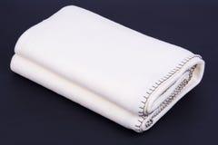 在黑暗的背景的白色羊毛毯子 免版税库存照片