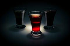 在黑暗的背景的红色和拖曳小玻璃在斑点点燃 免版税库存照片