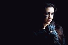 在黑暗的背景的美丽的积极的妇女 黑暗和神奇一个俏丽的女孩在与camoflauge油漆的阴影站立 免版税库存照片