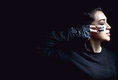 在黑暗的背景的美丽的积极的妇女 黑暗和神奇一个俏丽的女孩在与camoflauge油漆的阴影站立 免版税图库摄影