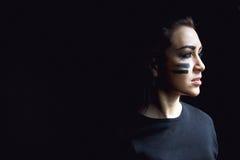 在黑暗的背景的美丽的积极的妇女 黑暗和神奇一个俏丽的女孩在与camoflauge油漆的阴影站立 库存照片
