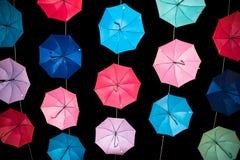 在黑暗的背景的色的开放伞 免版税图库摄影