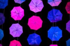 在黑暗的背景的色的开放伞 免版税库存照片