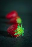 在黑暗的背景的草莓与水下落 免版税库存图片