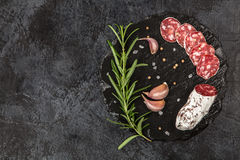 在黑暗的背景的蒜味咸腊肠 免版税库存照片