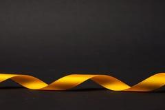 在黑暗的背景的金黄螺旋磁带 免版税库存图片