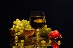 在黑暗的背景的静物画 酒酒玻璃、石榴和葡萄在篮子 库存照片