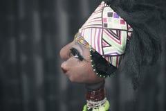 在黑暗的背景的非洲玩偶 图库摄影