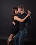 在黑暗的背景的年轻夫妇跳舞 免版税库存图片