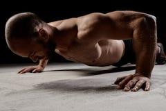 在黑暗的背景的年轻强有力的运动员训练俯卧撑 免版税库存照片