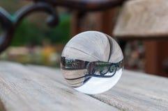 在黑暗的背景的玻璃透明球,木 免版税库存照片