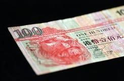 在黑暗的背景的100香港美元 免版税库存照片
