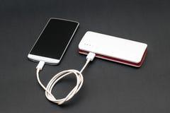 在黑暗的背景的Powerbank充电的智能手机 免版税库存照片