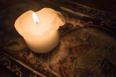 在黑暗的蜡烛在一张被仿造的桌上 库存照片