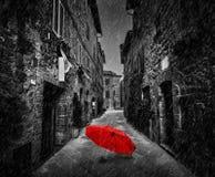 在黑暗的街道上的伞在一个老意大利镇在托斯卡纳,意大利 下雨 免版税库存图片