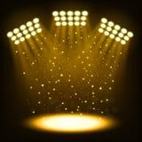 在黑暗的金背景的明亮的体育场聚光灯 免版税库存照片