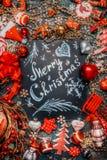 在黑暗的黑板的圣诞快乐字法和在黑暗的土气背景,顶视图,框架的各种各样的红色假日装饰 库存图片