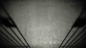 在黑暗的水泥监狱地板上的监狱牢房门闭合值的阴影 股票录像
