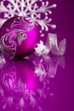 在黑暗的紫色背景的紫色和银色圣诞节装饰品 免版税库存照片