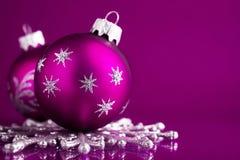 在黑暗的紫色xmas背景的紫色和银色圣诞节装饰品 免版税图库摄影