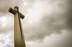 在黑暗的clounds的十字架 库存照片