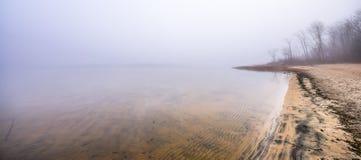 在11月早晨雾的偏僻的空的海滩 图库摄影