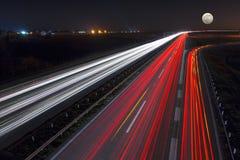 在满月晚上加速驾驶在高速公路 免版税库存图片