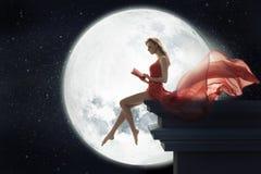在满月背景的逗人喜爱的妇女 库存图片