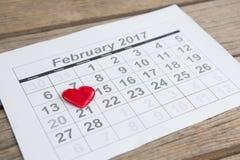 在2月14日日历的日期安置的红色心脏形状 库存照片