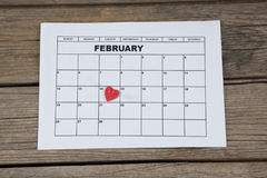 在2月14日日历的日期安置的红色心脏形状 库存图片
