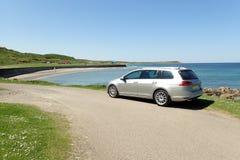 在晴朗的全景的银色旅行车与路,海滩,海 库存照片