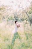 在晴朗的公园中间长的白色礼服的新娘拿着巨大的桃红色花束 回到视图 免版税图库摄影