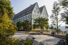 在晴朗的冬天mornin遮荫植物和树的异乎寻常的大厦  免版税库存照片
