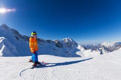 在晴朗的天气的男孩滑雪有山景 库存照片