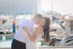 在晴朗的户外背景的愉快的亲吻的爱恋的夫妇 免版税库存照片