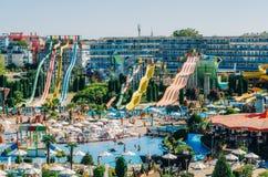 水在晴朗的海滩的公园行动全景以幻灯片和游泳池的数量孩子和成人的 免版税库存图片