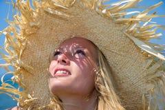 在晴朗的海滩的白肤金发的佩带的草帽 免版税库存图片