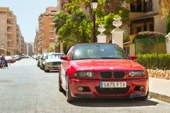 在晴朗的街道,托雷维耶哈上的红色现代小轿车车BMW M3系列, 免版税库存图片
