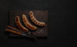 在黑木板的油煎的香肠 库存图片
