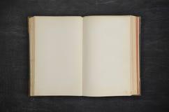 在黑木头的老开放书 免版税图库摄影