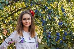 在洋李附近的美丽的塞尔维亚女孩 免版税库存图片