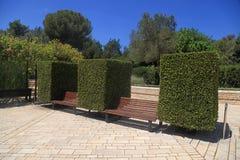 在黄杨木潜叶虫之间的庭院长凳 免版税库存图片