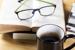 在黑杯子和书堆的咖啡 免版税库存照片